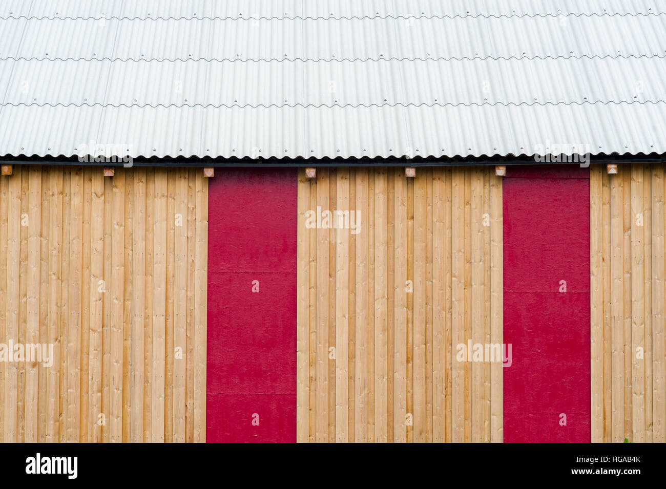Side view of a wooden warehouse with red insets and white laminated roof - Stock Image
