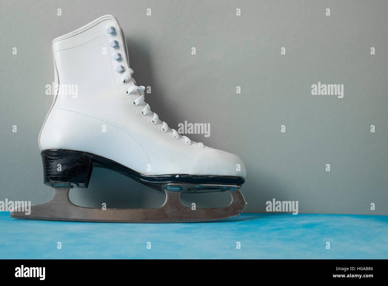 Vintage ice skate on the gray/blue vintage background - Stock Image