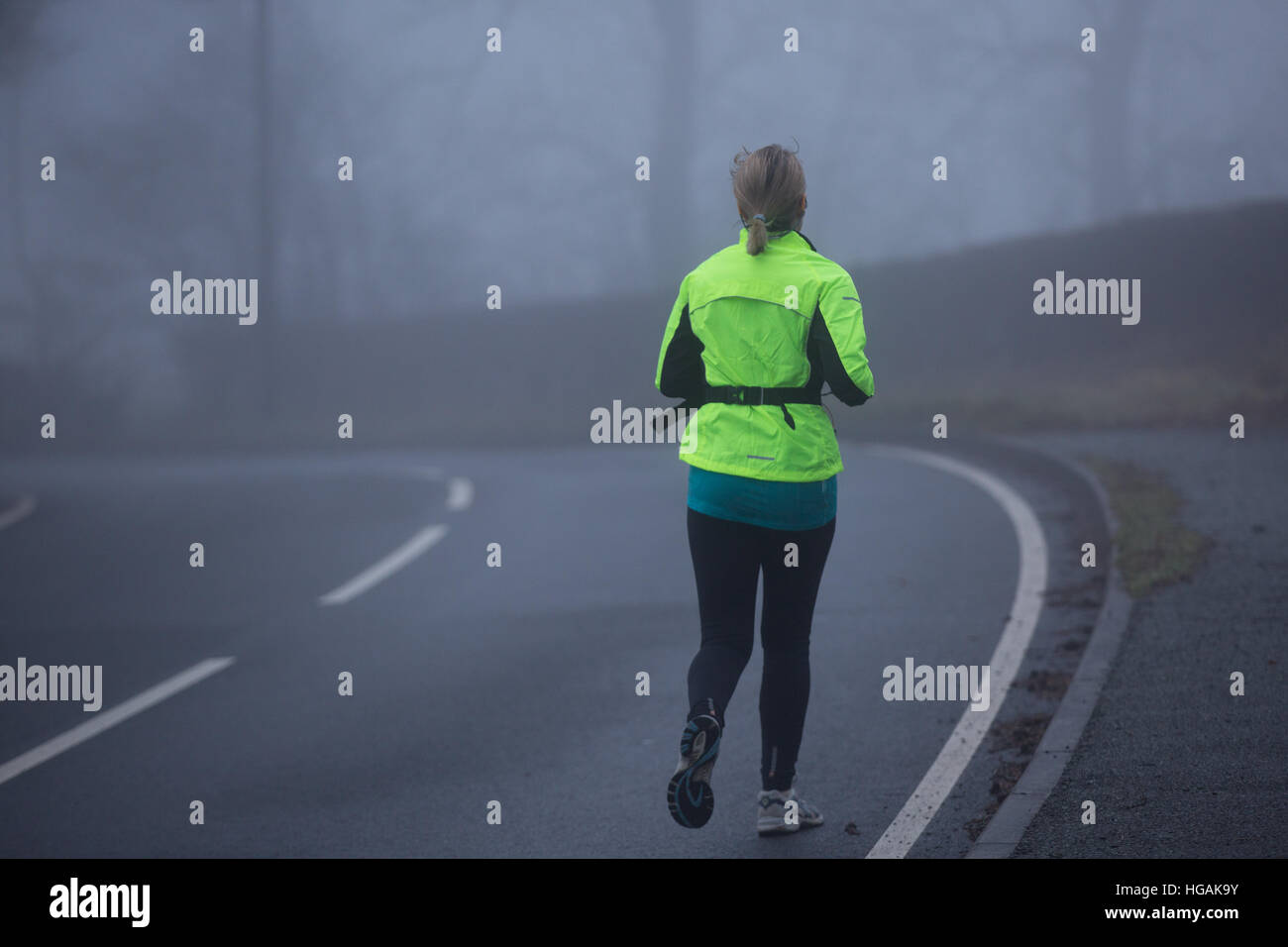 A female jogger wearing Hi Viz while jogging along the B4343 as the thick fog hampers visibility this morning. © Stock Photo