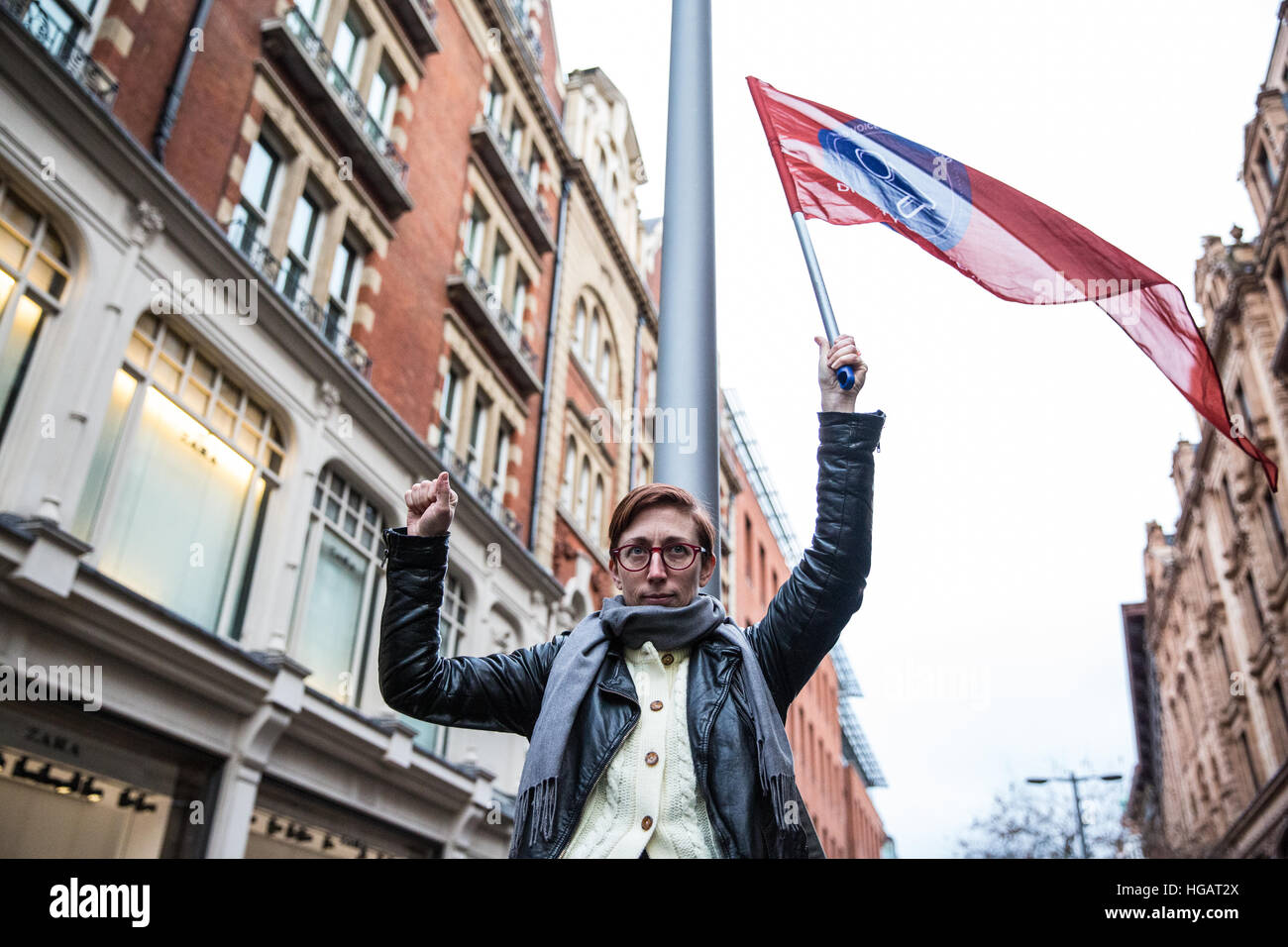 London, UK. 7th January, 2017. A supporter of United Voices of the World trade union holds the trade union's - Stock Image