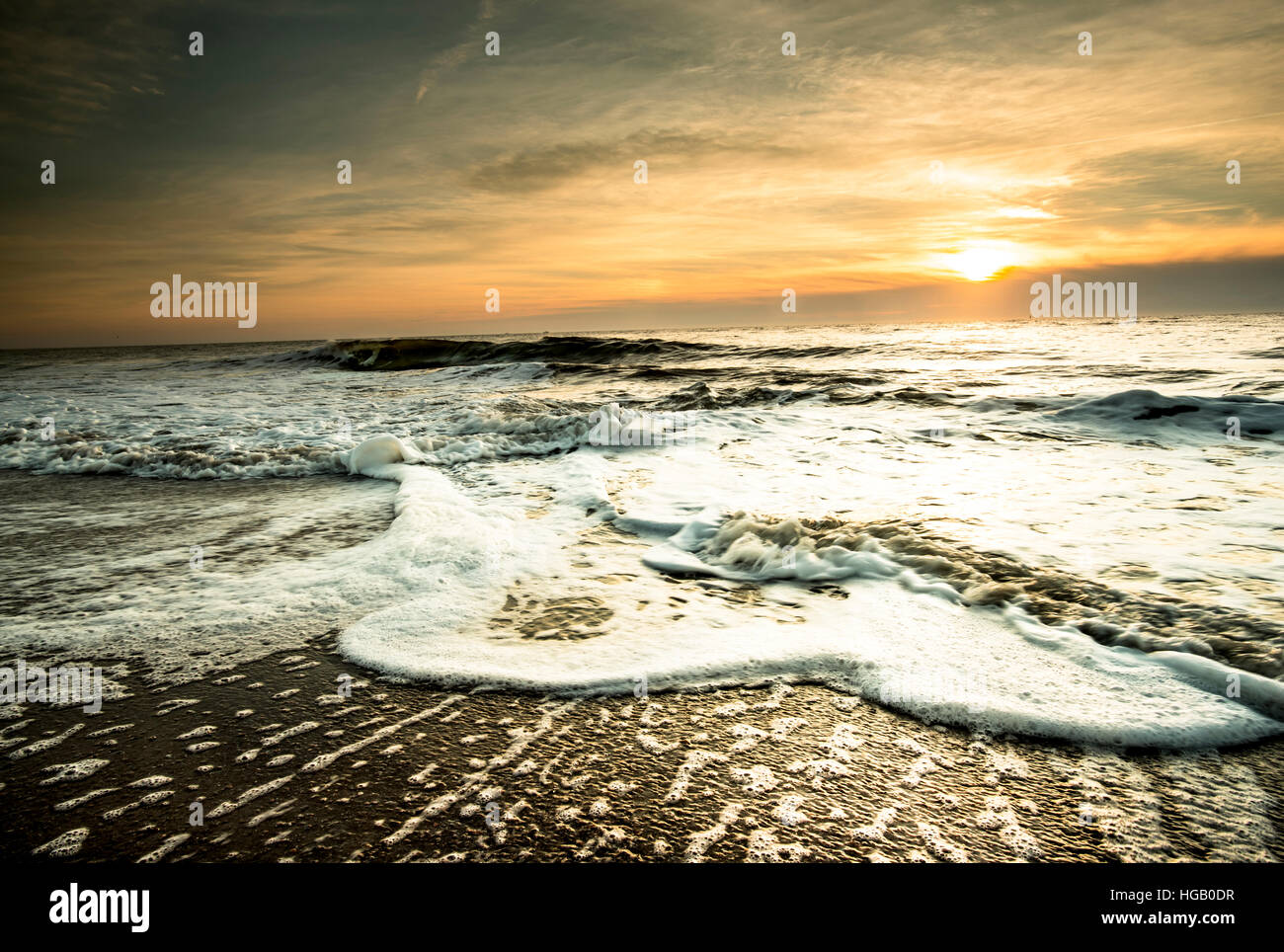 Tyee Beach, Savannah, Georgia at Sunrise.  Foam, Waves, Sand with a high Overcast Sky in Warm Brown Tones - Stock Image