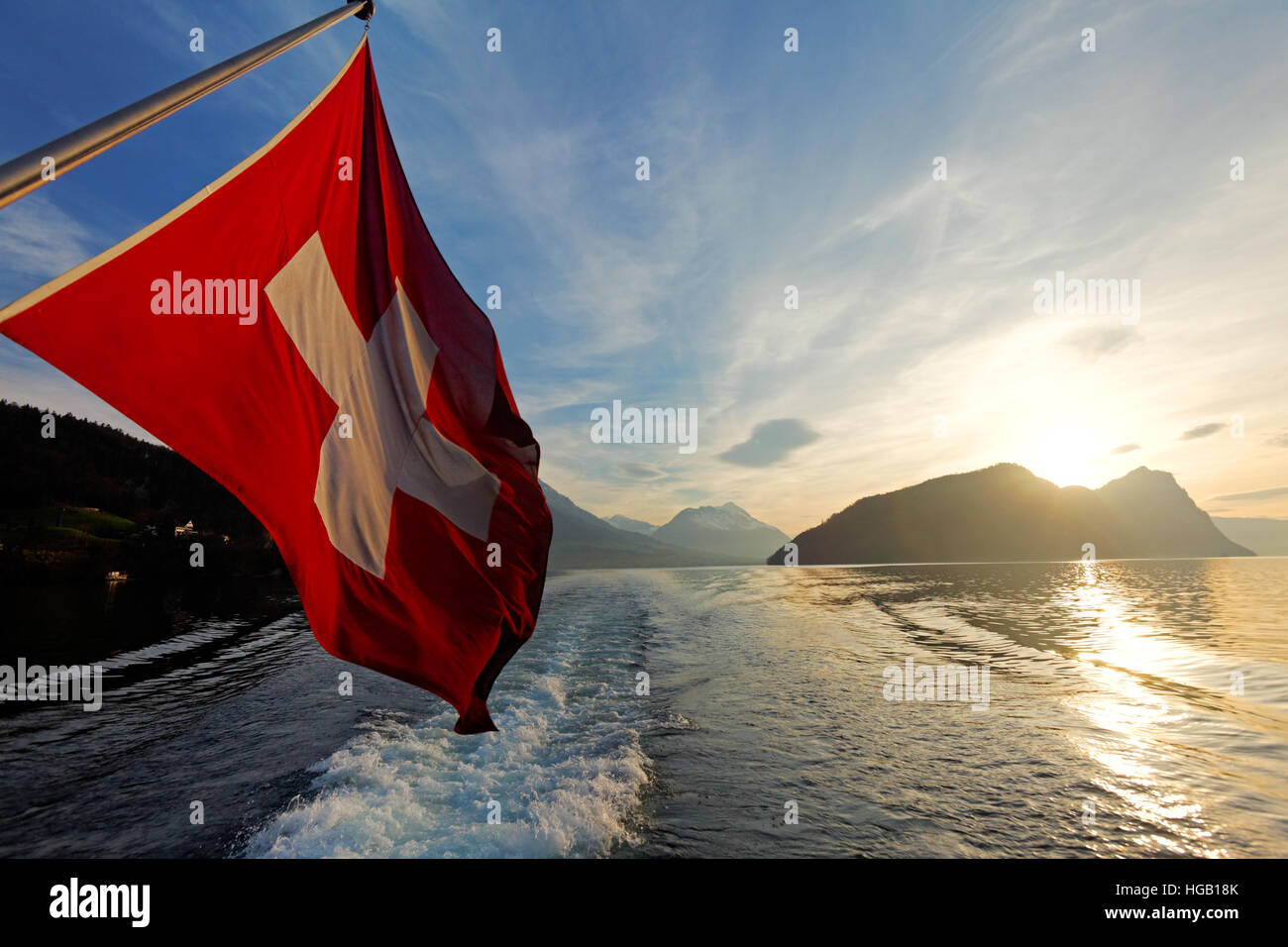 Swiss flag on tour boat cruising Lake Lucerne as sun sets over the Alp mountains, Switzerland - Stock Image