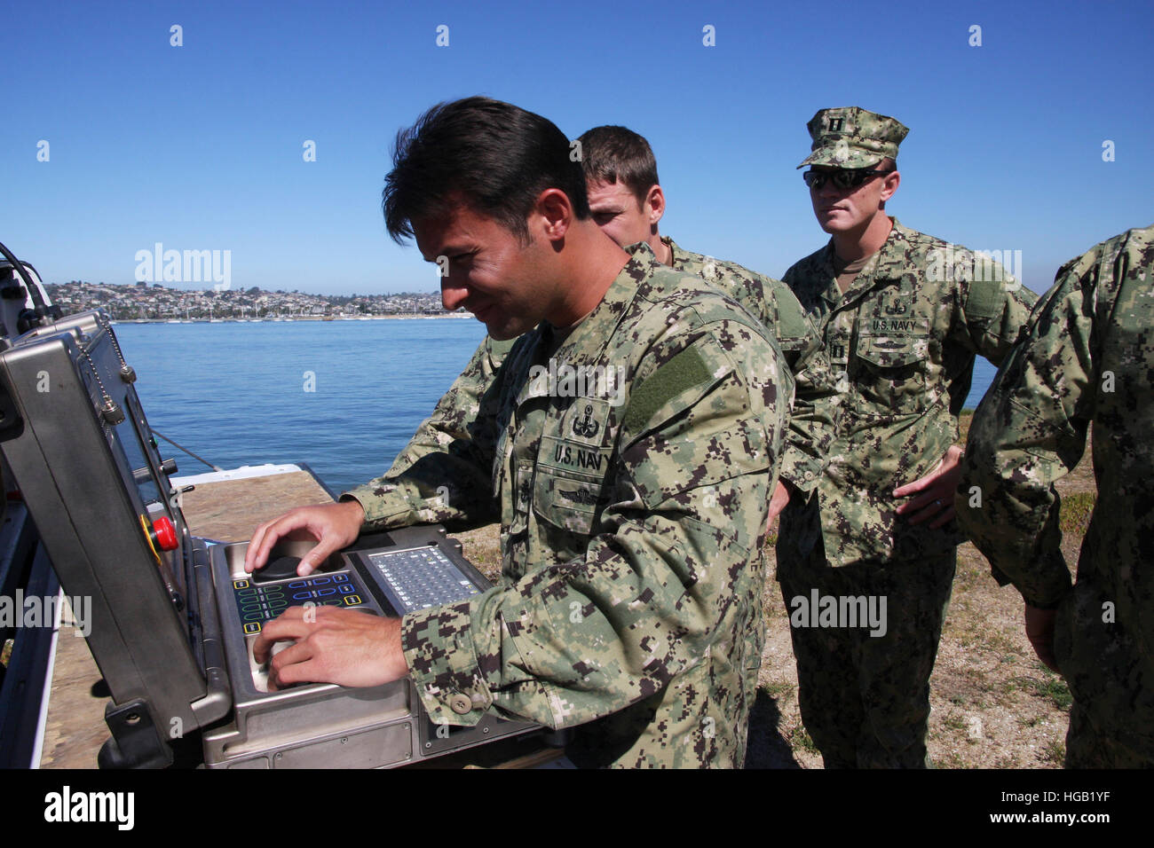 EOD members operate a remote controlled robot from computer system. - Stock Image