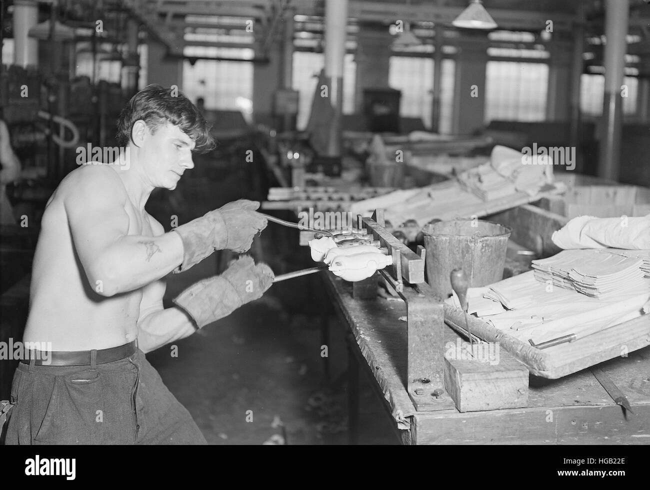 Worker stripping rubber bodies off core-bars while making dolls, 1936. - Stock Image