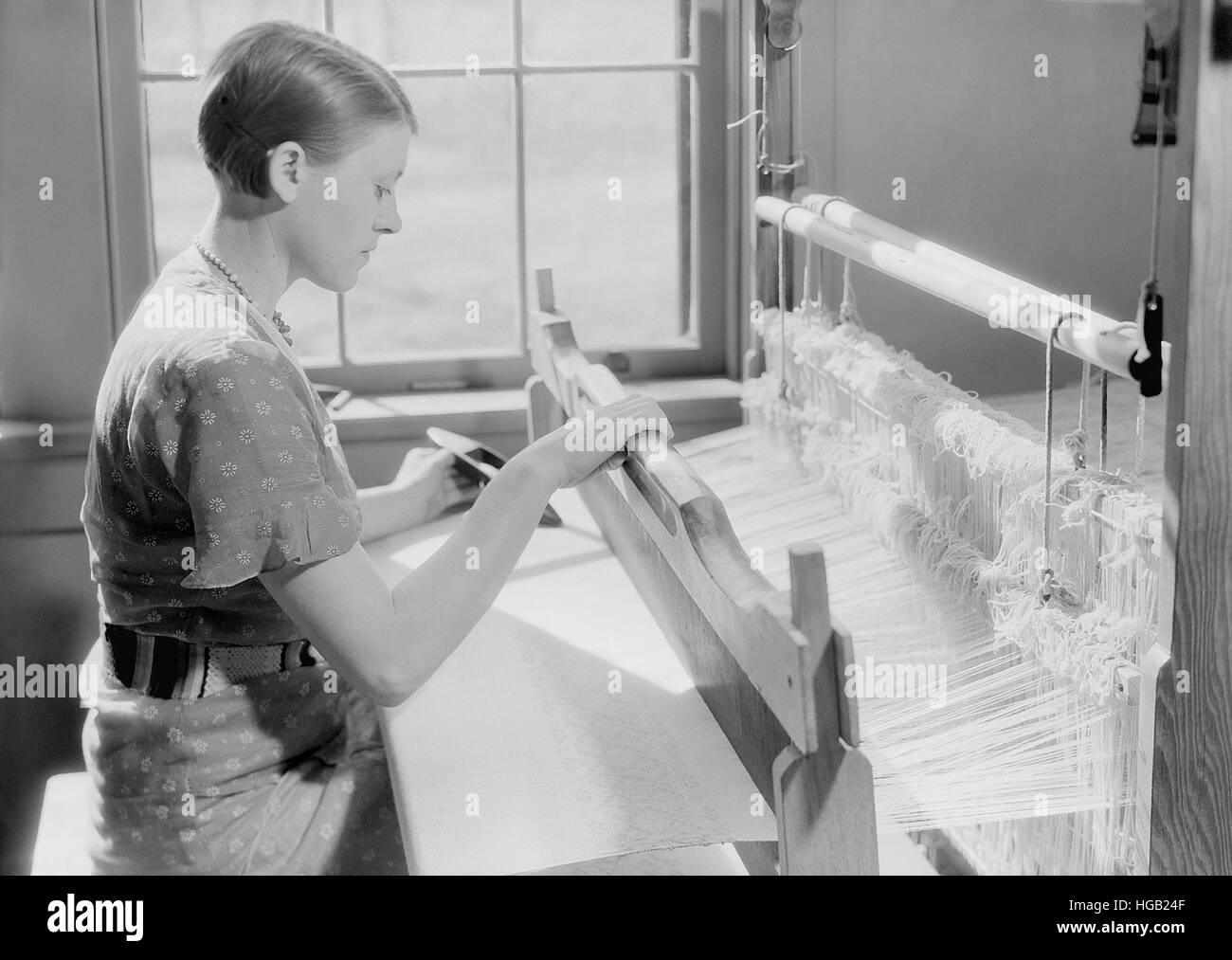 Woman weaving a baby blanket, 1933. - Stock Image