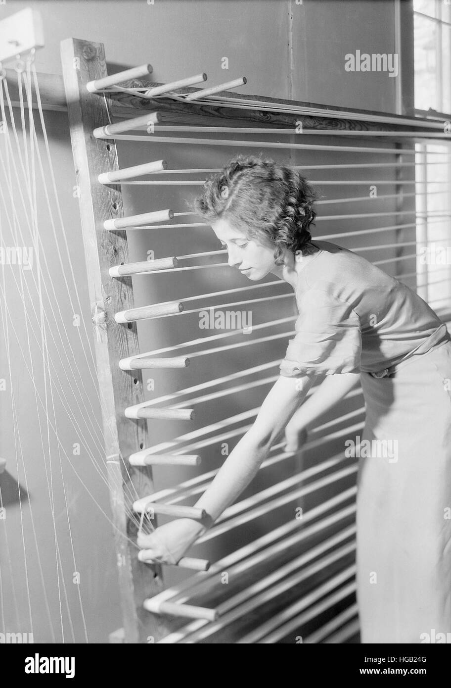 Woman preparing warp for weaving, 1933. - Stock Image