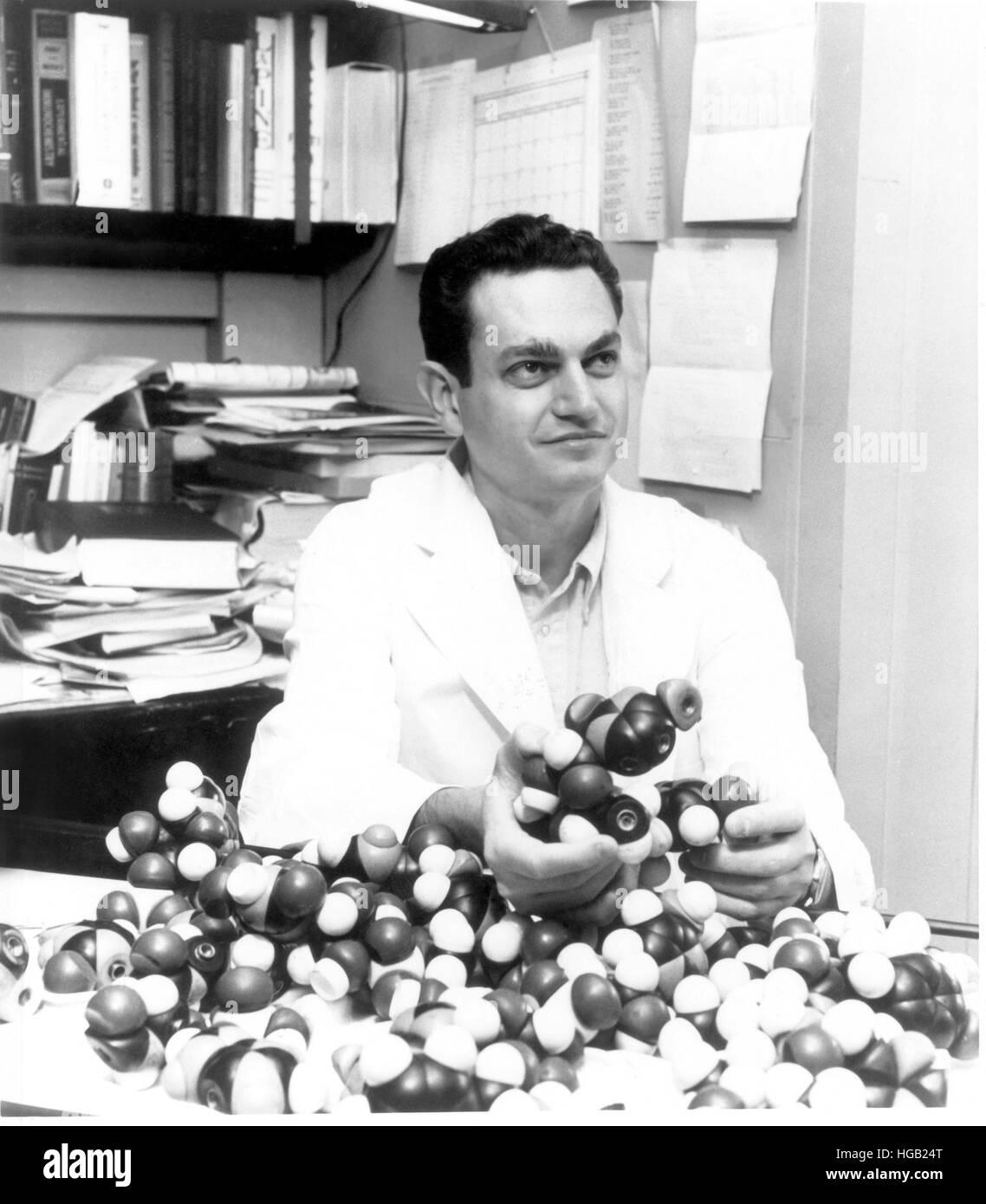 Dr. Marshall Nirenberg holding DNA models. - Stock Image