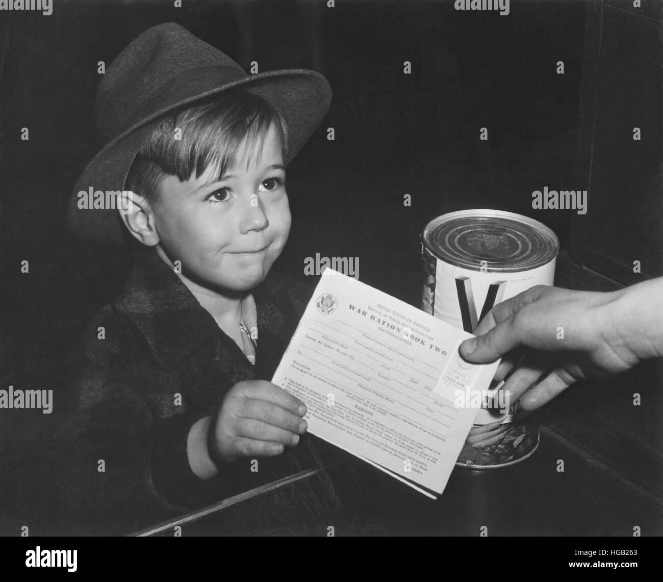 An eager school boy gets his first experience in using War Ration Book Two. circa 1943 Stock Photo