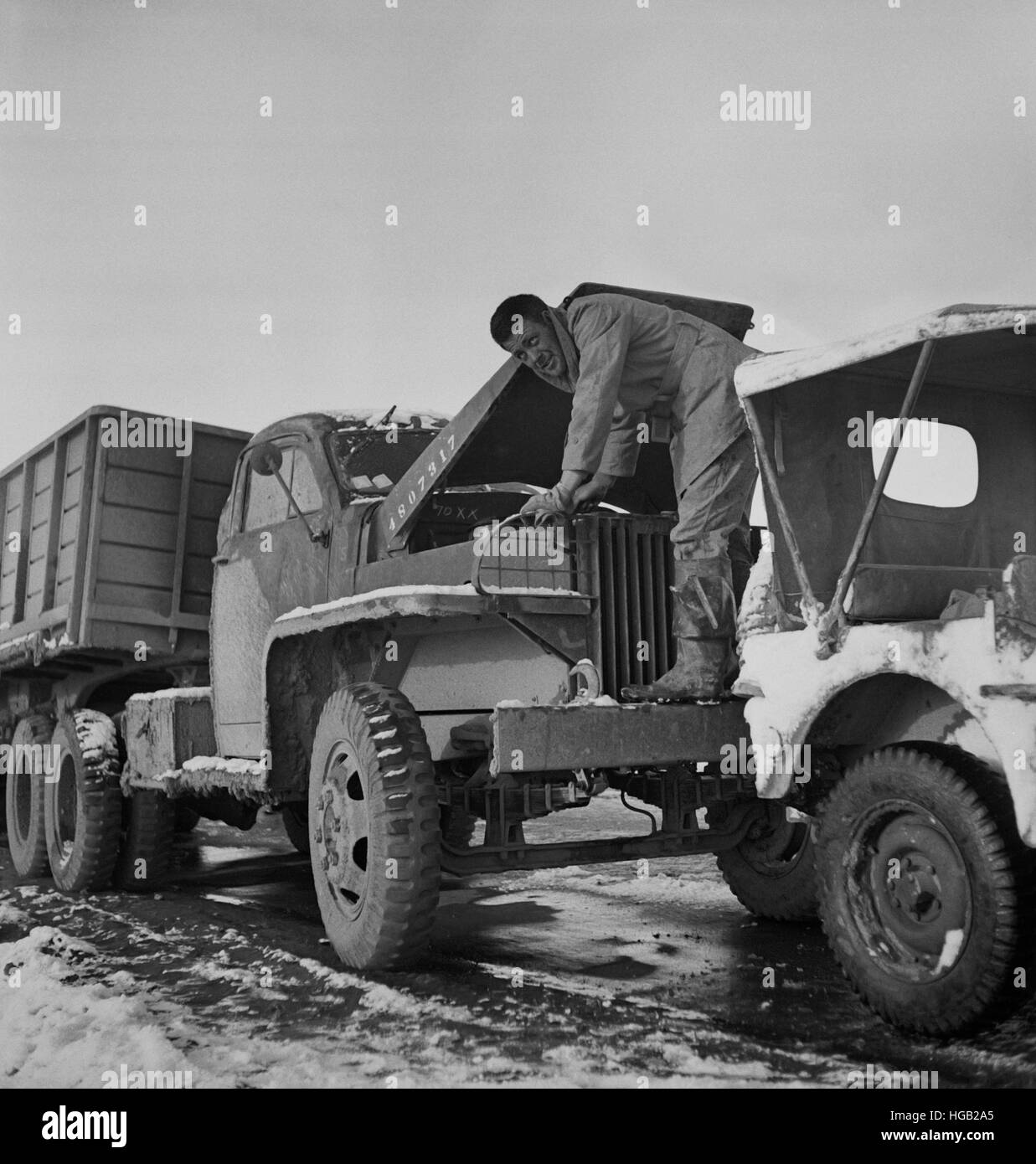 A truck driver with the U.S. Army checking the oil. - Stock Image