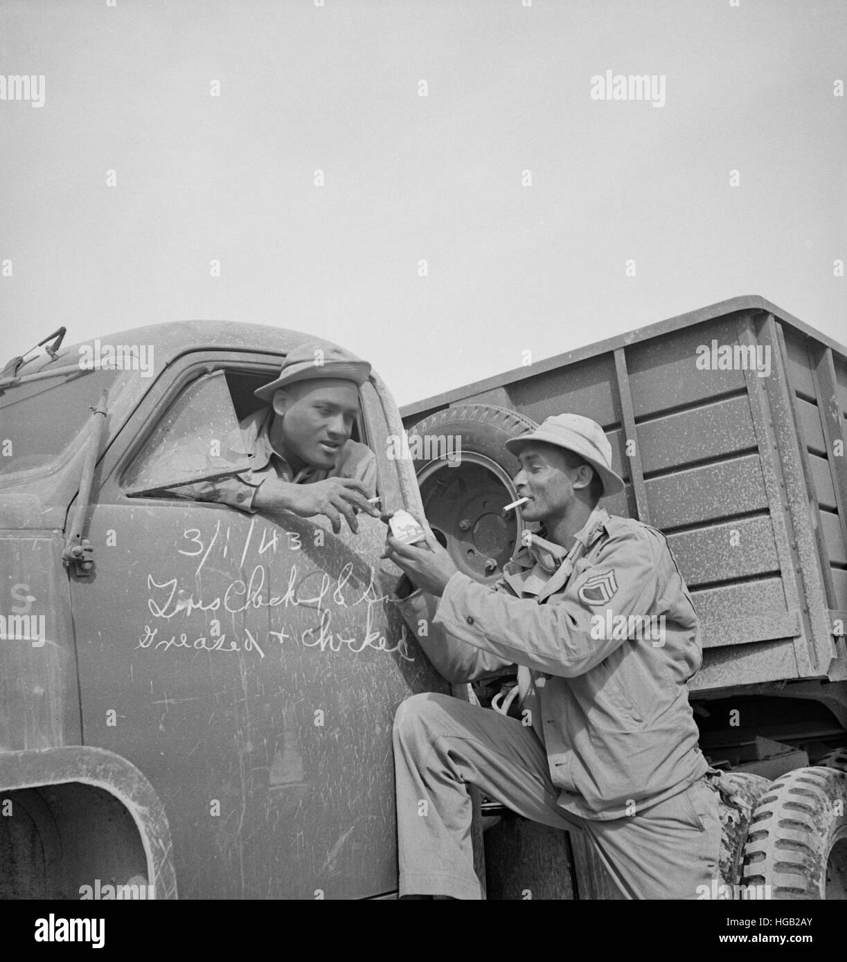 Drivers of a U.S. Army truck convoy stops to have a smoke on the desert, 1943. - Stock Image