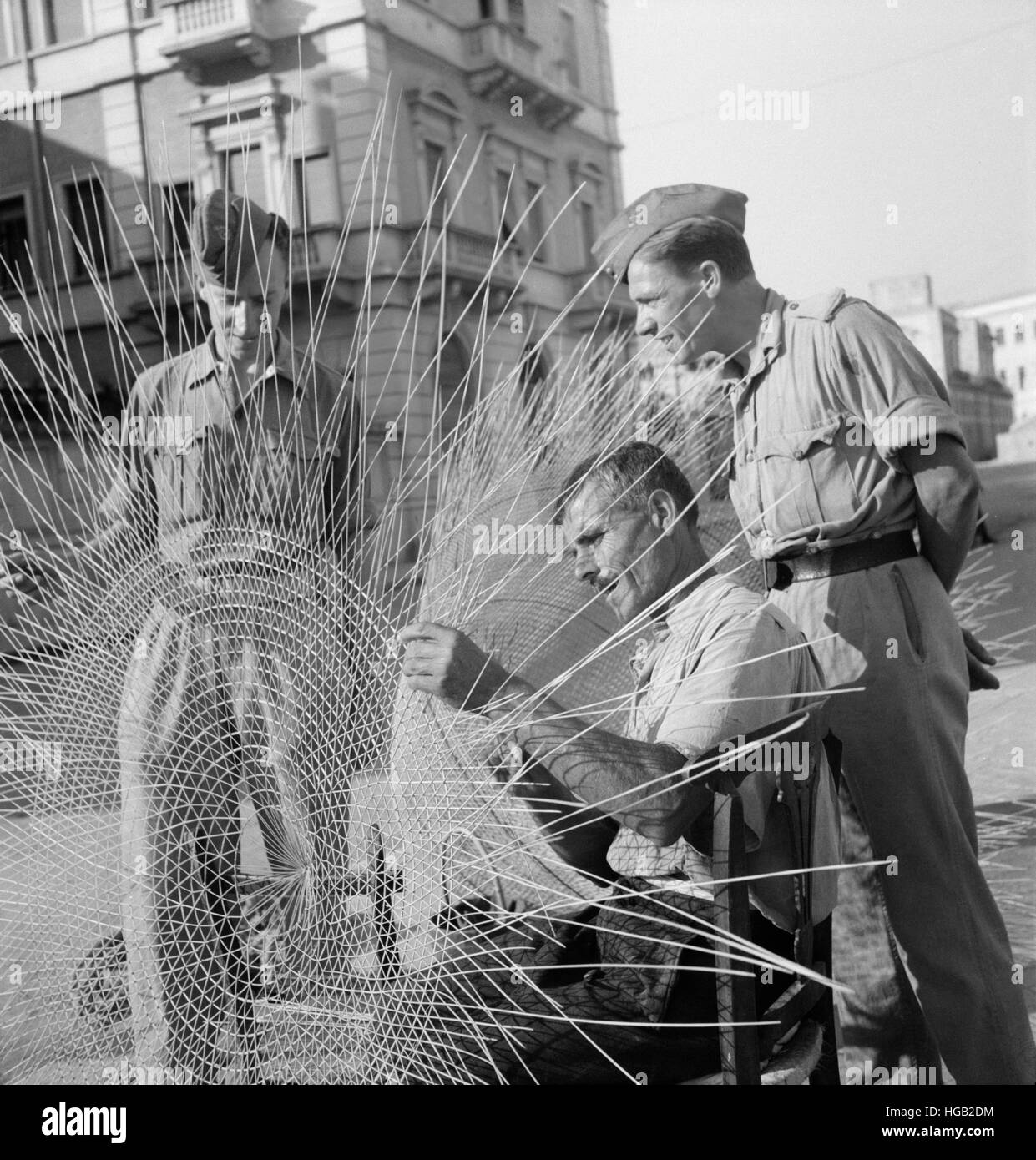 A Sicilian weaving fish nets on the streets of Sicily, 1943. - Stock Image