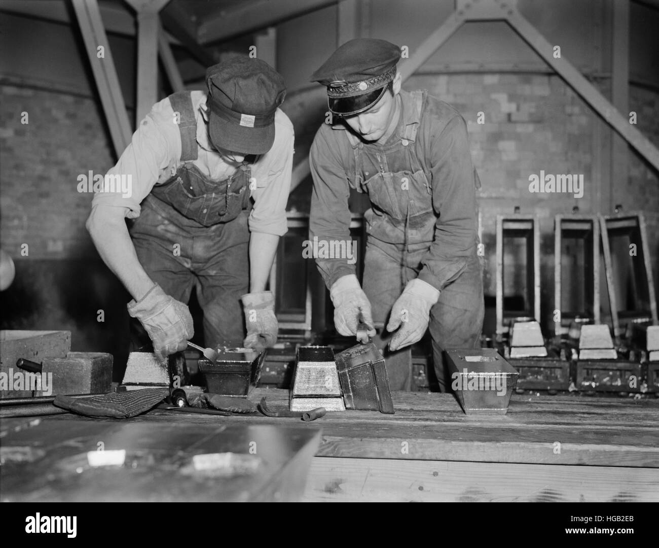 Bars of pure tin are trimmed and cleaned before removal from their mold, 1942. - Stock Image