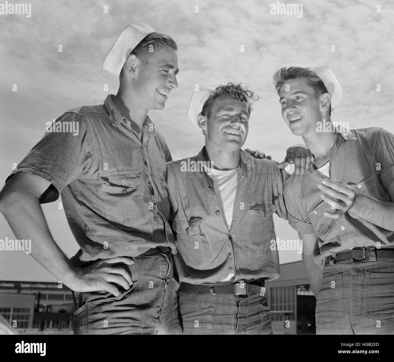 Sailor mechanics laugh over a good story between servicing operations on Navy planes, 1942. - Stock Image