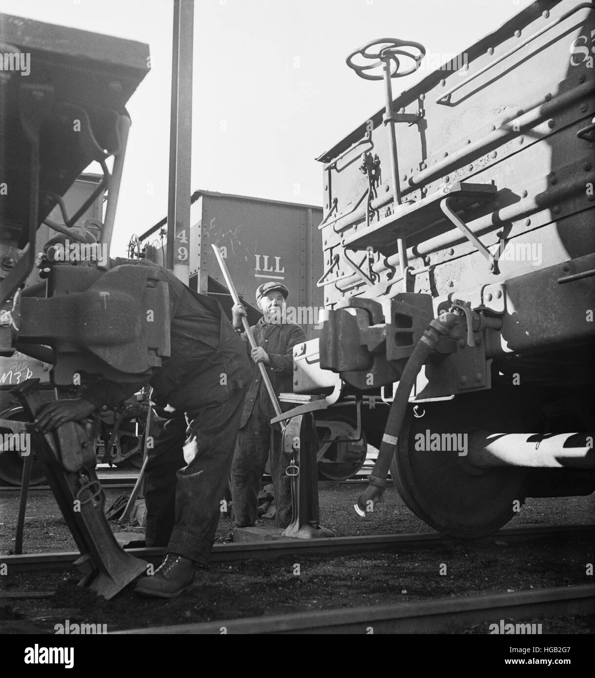 Jacking up a car on the repair tracks at an Illinois Central Railroad yard, 1942. - Stock Image