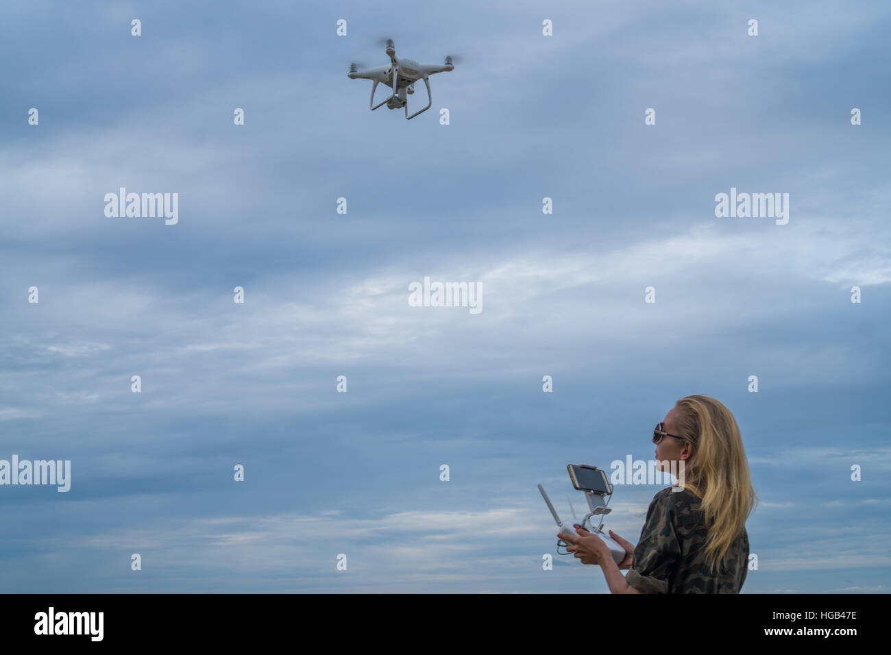 Happy woman standing with remote controller of drone over cloudy sky background - Stock Image