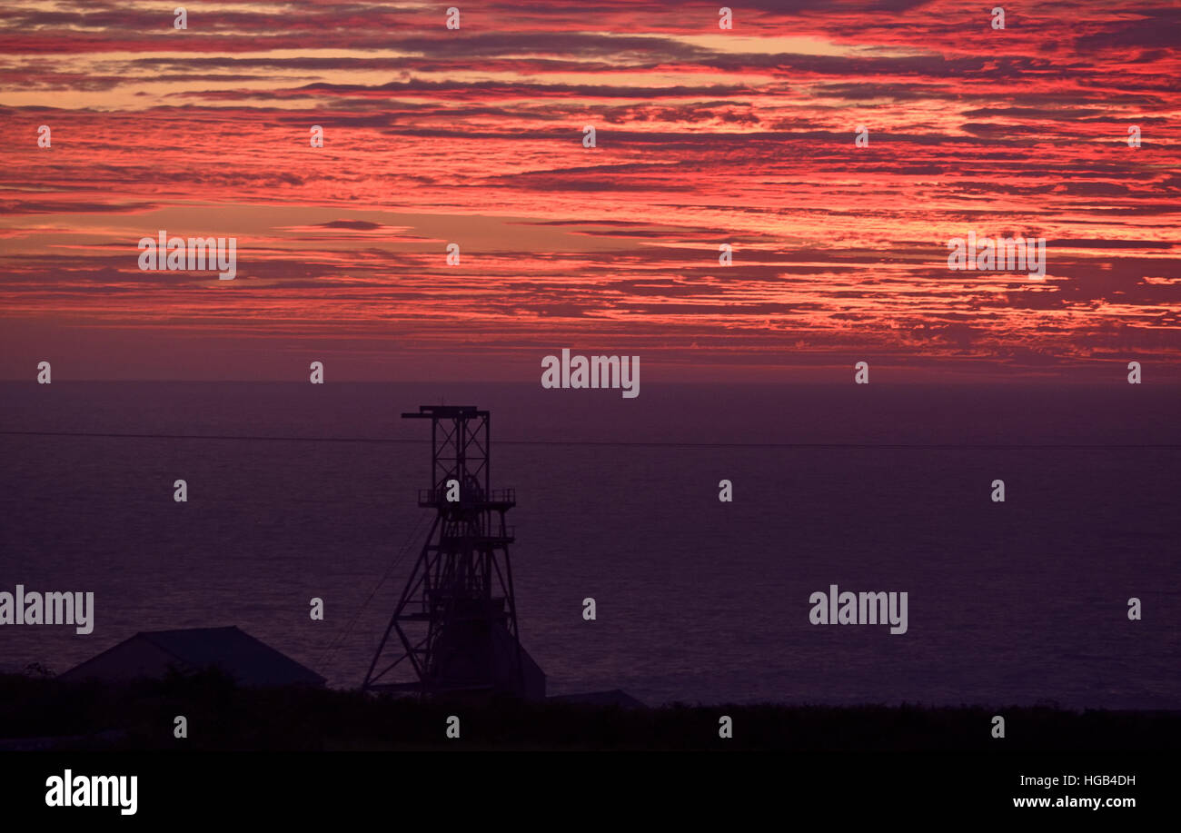 Geevor Tin Mine, Pendeen, Penwith Cornwall, south-west Britain UK silhouetted against red sunset sky. On the south - Stock Image