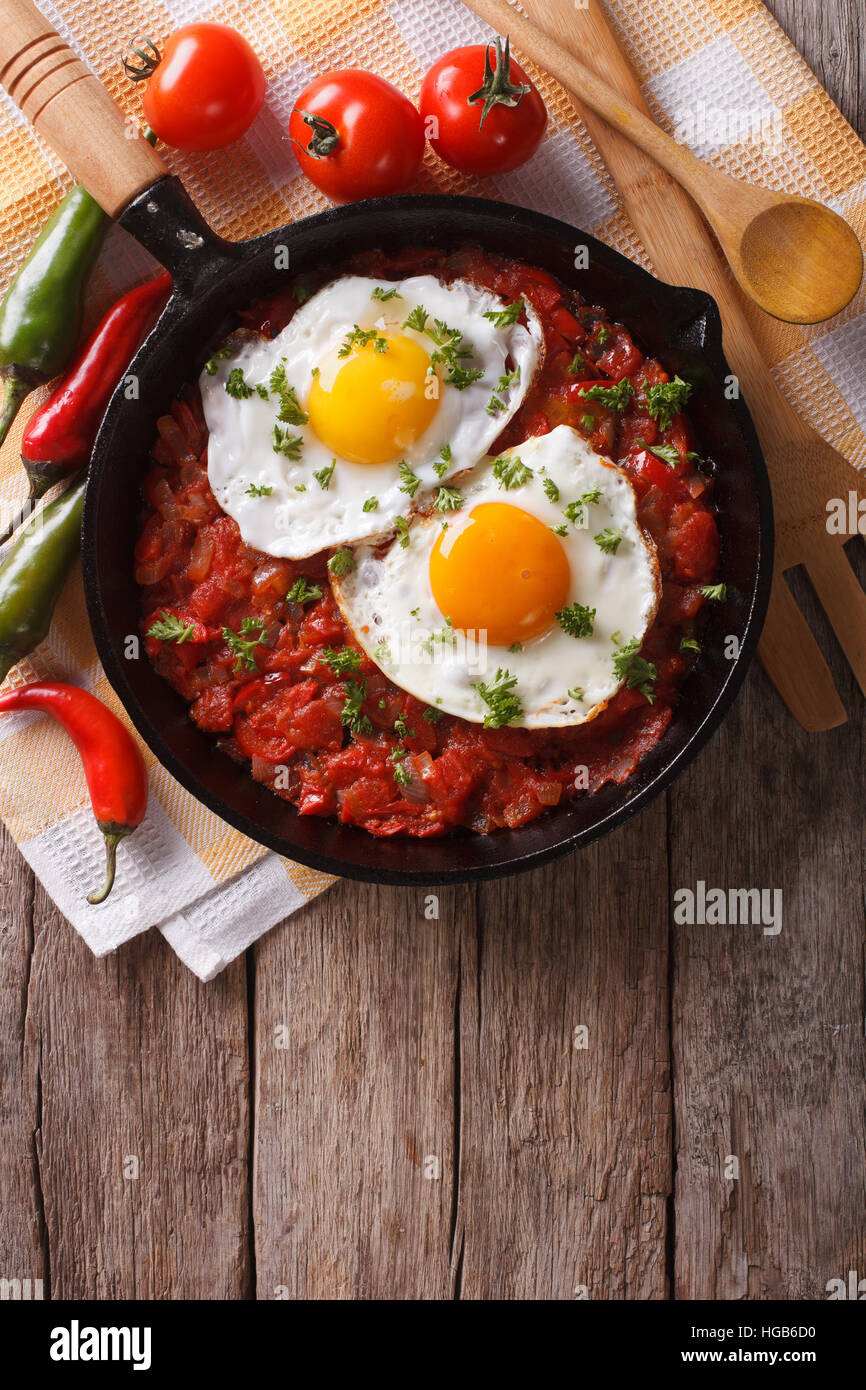 huevos rancheros closeup in the pan and ingredients on the table, vertical view from above - Stock Image