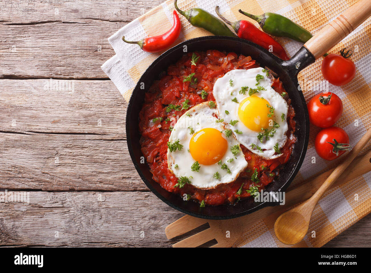 Mexican fried eggs huevos rancheros close-up in a frying pan on the table. horizontal view from above - Stock Image