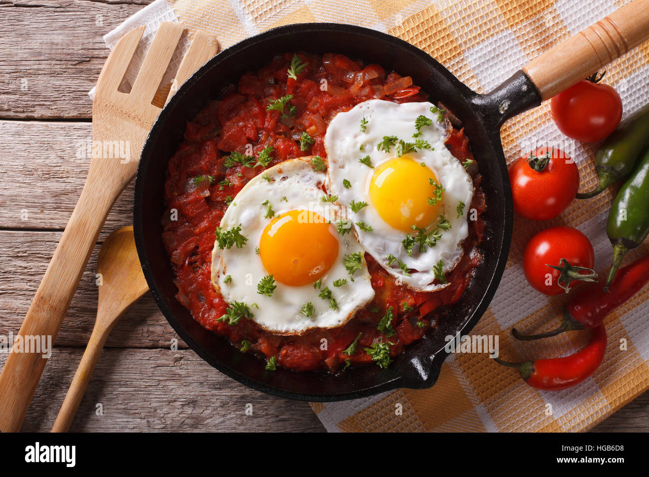 huevos rancheros closeup in the pan and ingredients on the table, horizontal view from above - Stock Image
