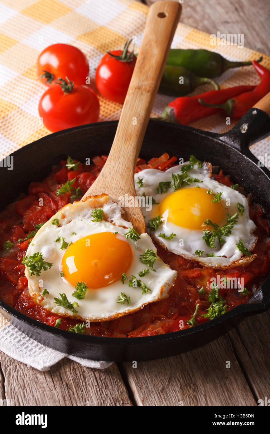 Traditional Mexican breakfast fried egg with salsa closeup in the pan. vertical - Stock Image