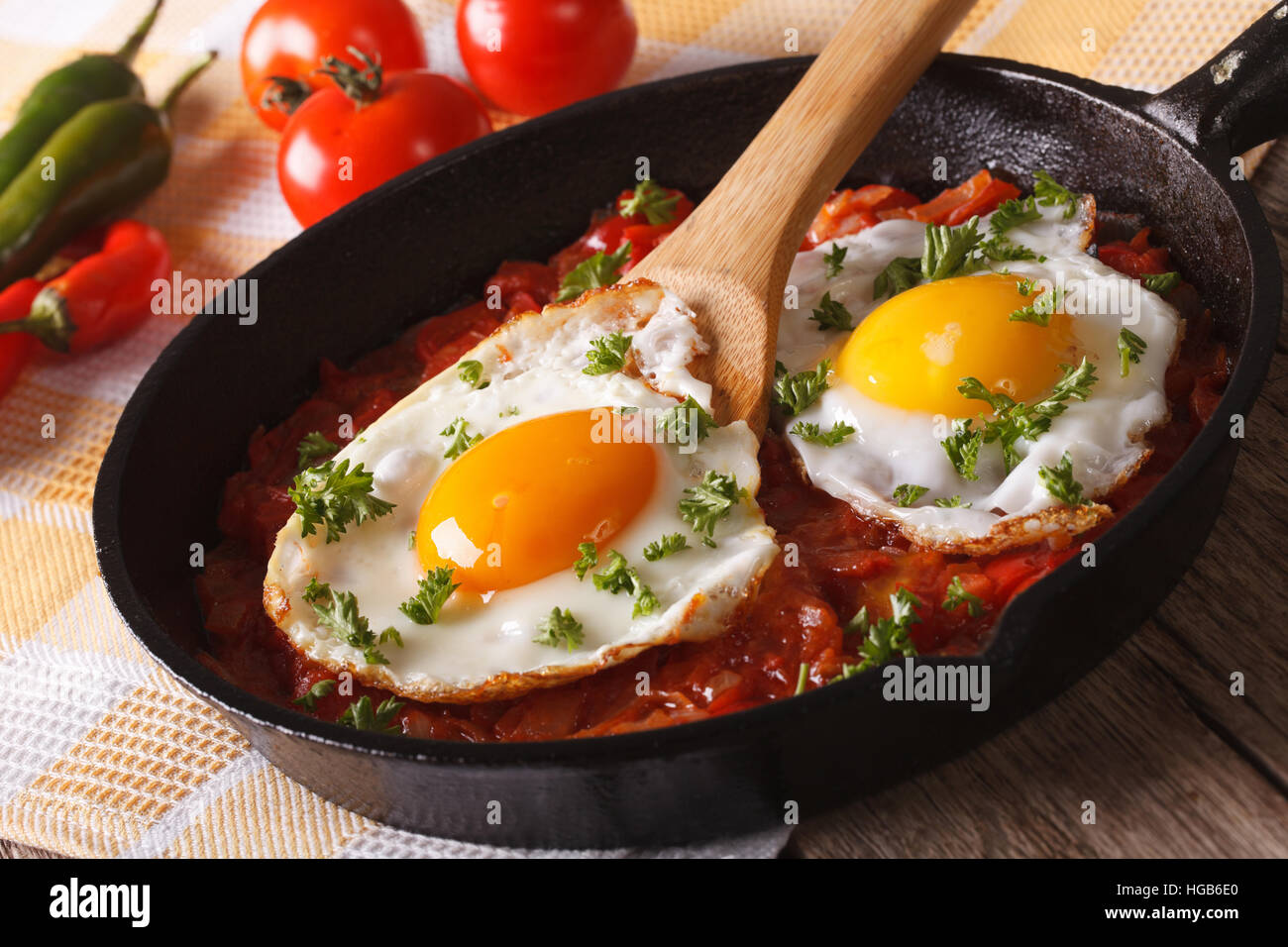 Mexican breakfast huevos rancheros: fried egg with salsa closeup in the pan. Horizontal - Stock Image