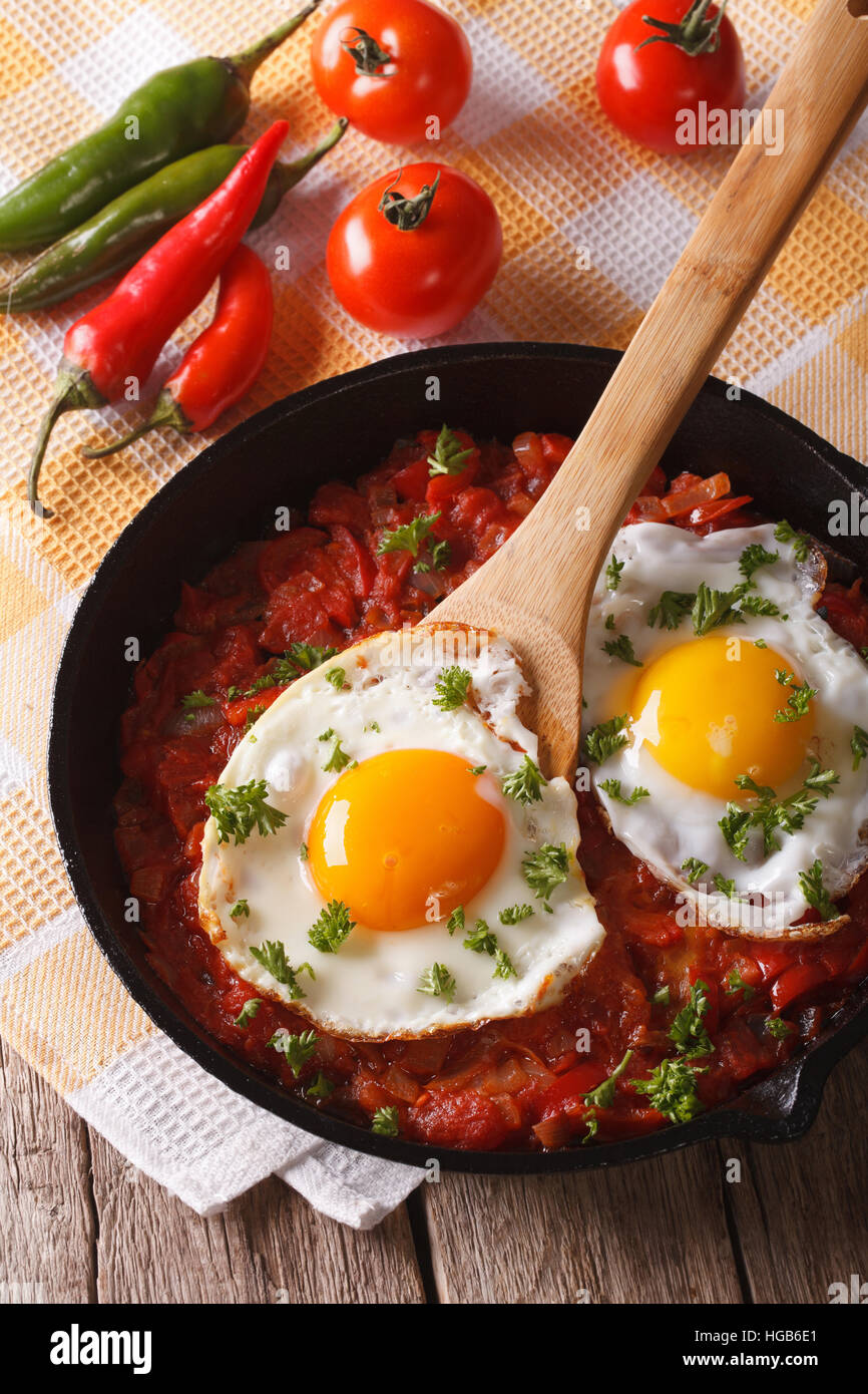 huevos rancheros: fried egg with salsa closeup in the pan. vertical - Stock Image