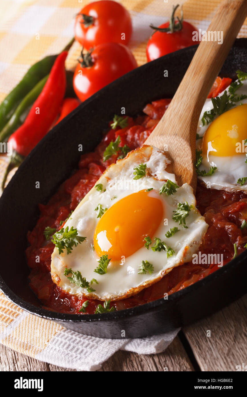Mexican breakfast huevos rancheros: fried egg with salsa closeup in the pan. vertical - Stock Image