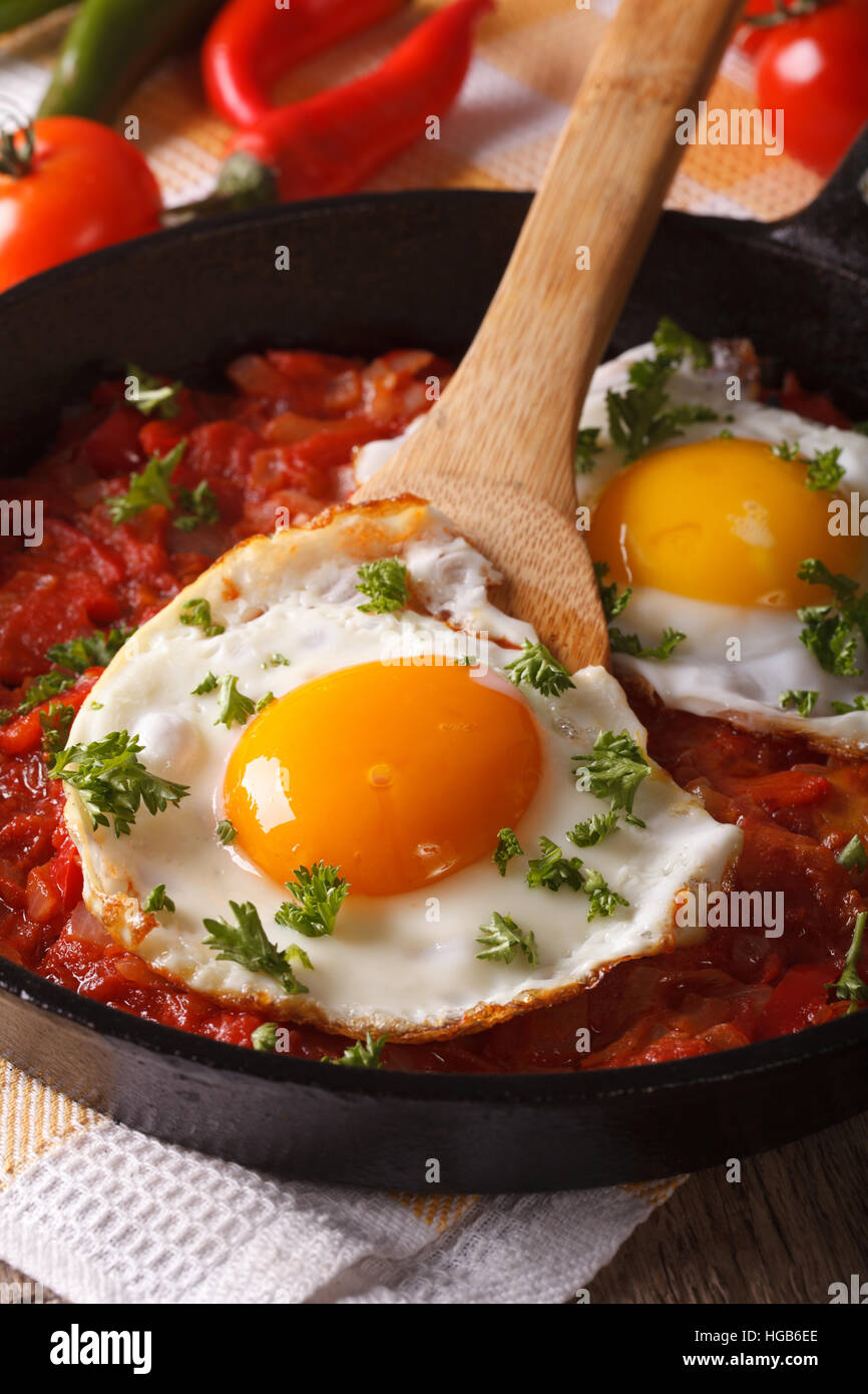 Mexican breakfast: fried egg with salsa on a frying pan macro. vertical - Stock Image