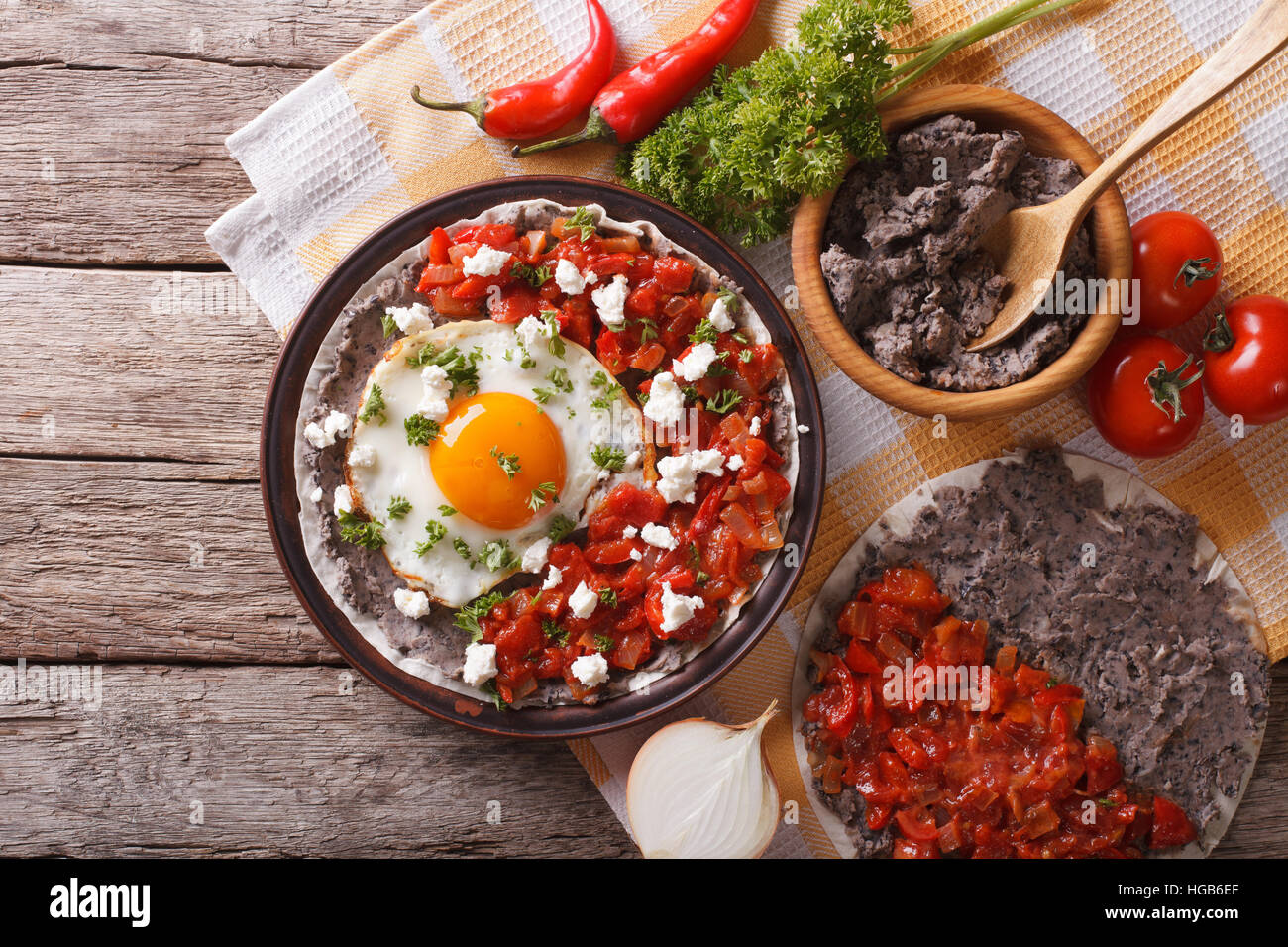 Mexican breakfast: huevos rancheros on the plate on the table. horizontal view from above - Stock Image