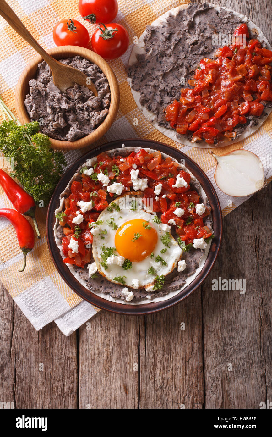 Mexican breakfast: huevos rancheros on the plate on the table. vertical view from above - Stock Image