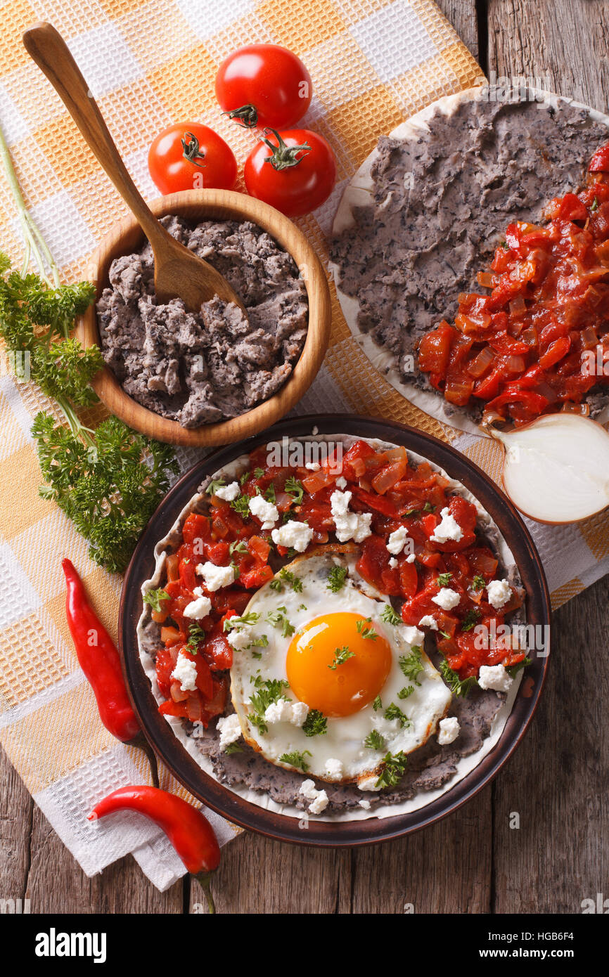 Mexican breakfast: huevos rancheros on the plate close-up on the table. Vertical view from above - Stock Image