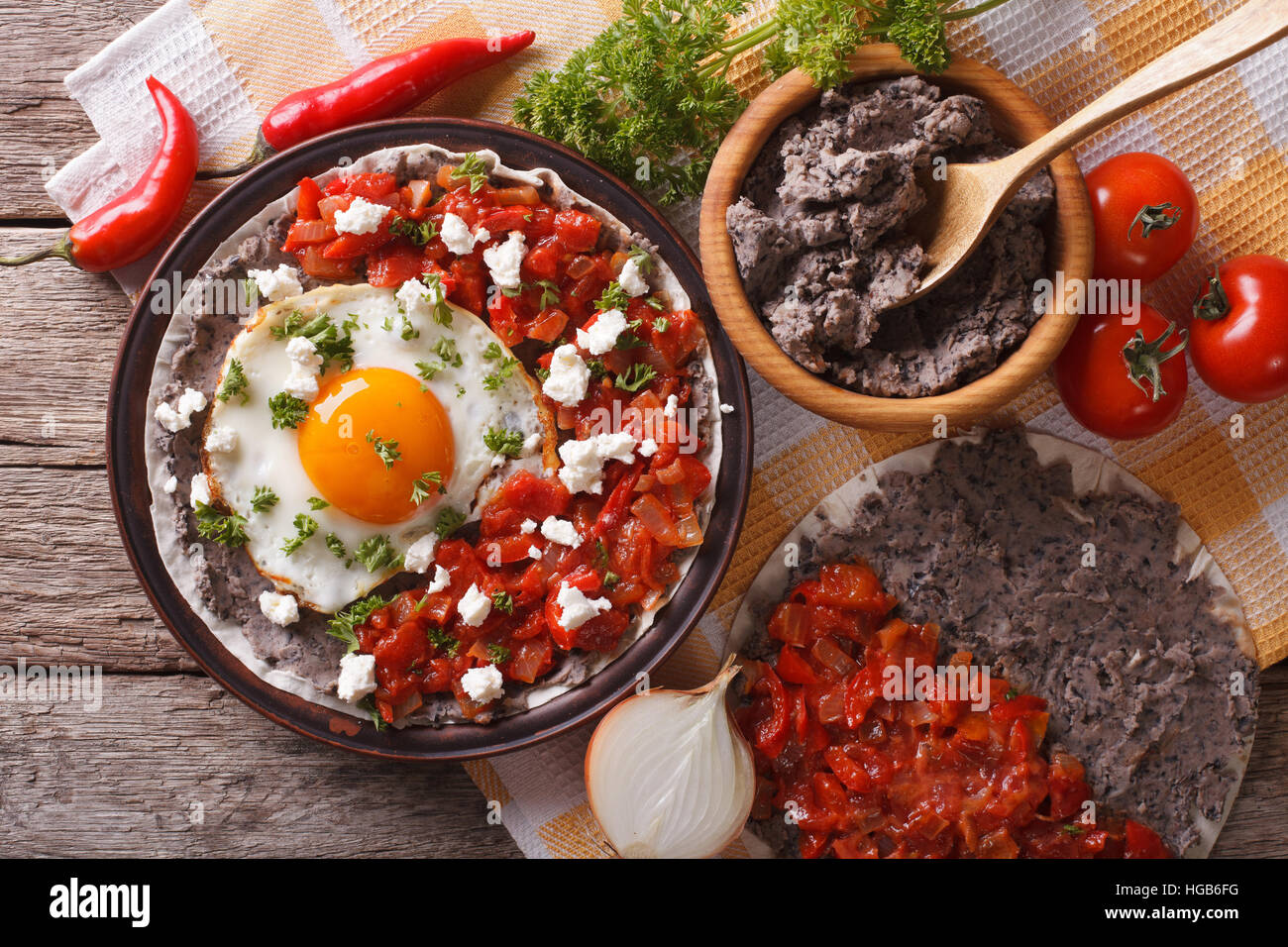 Mexican breakfast: huevos rancheros on the plate close-up on the table. horizontal view from above - Stock Image