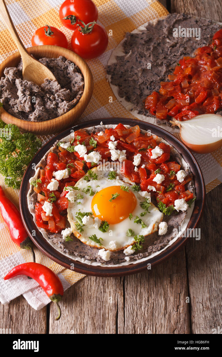 Mexican breakfast: fried egg with salsa on the plate close-up on the table. vertical - Stock Image