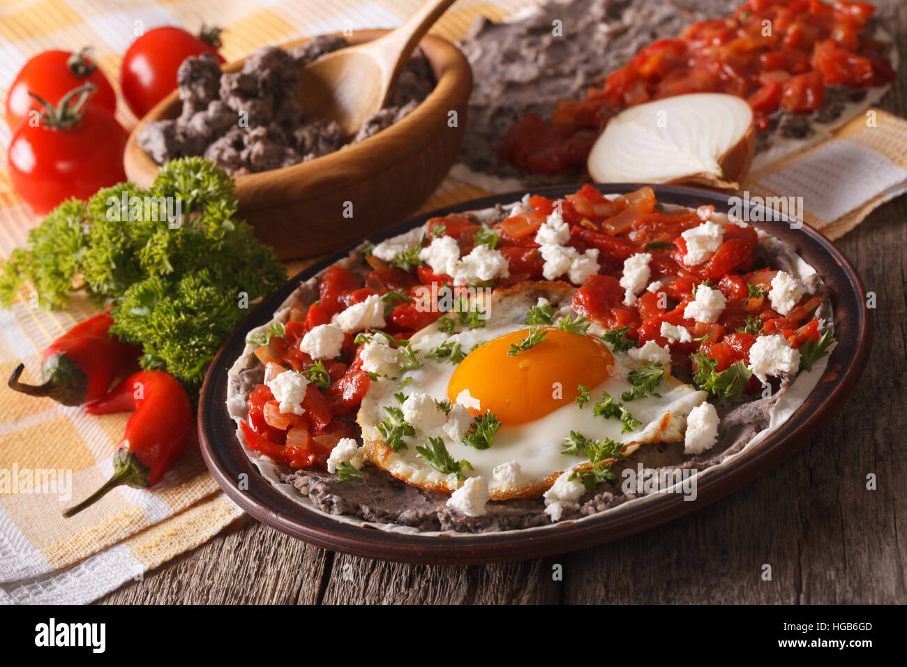 Mexican fried eggs huevos rancheros and ingredients close-up on the table. Horizontal - Stock Image