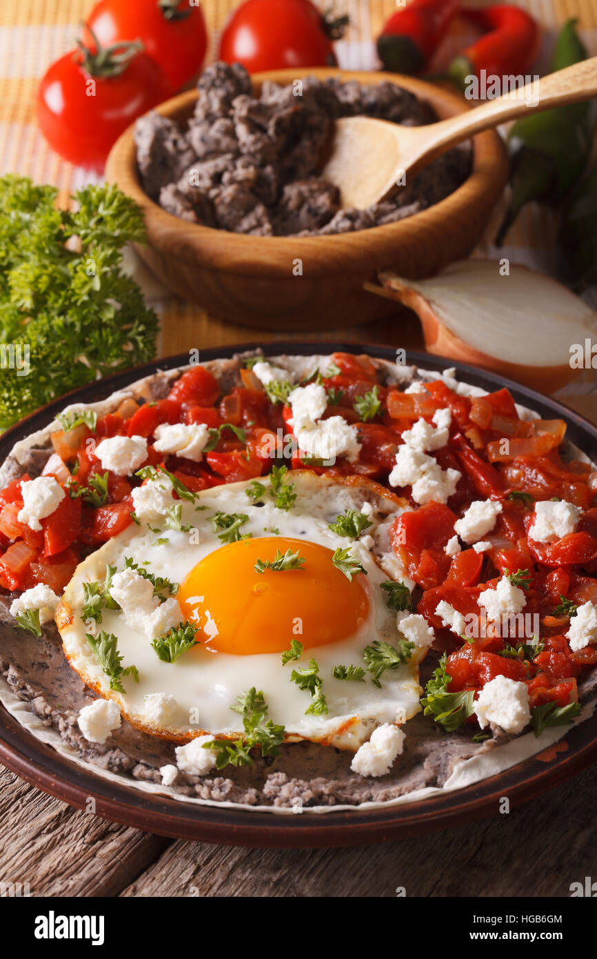 Mexican fried eggs huevos rancheros and ingredients close-up on the table. vertical - Stock Image
