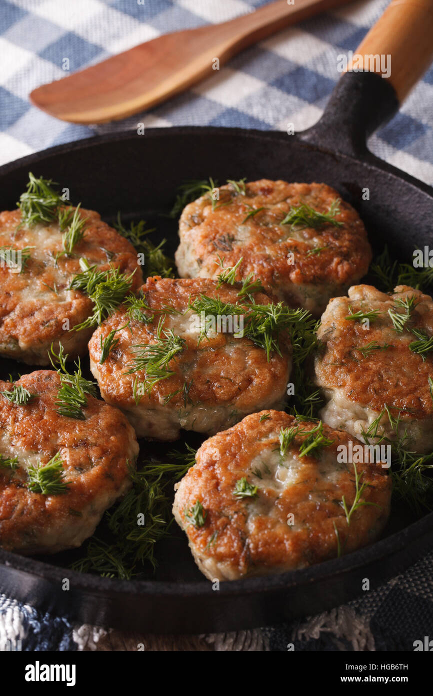 fishcakes with herbs close-up in a pan on the table. vertical - Stock Image