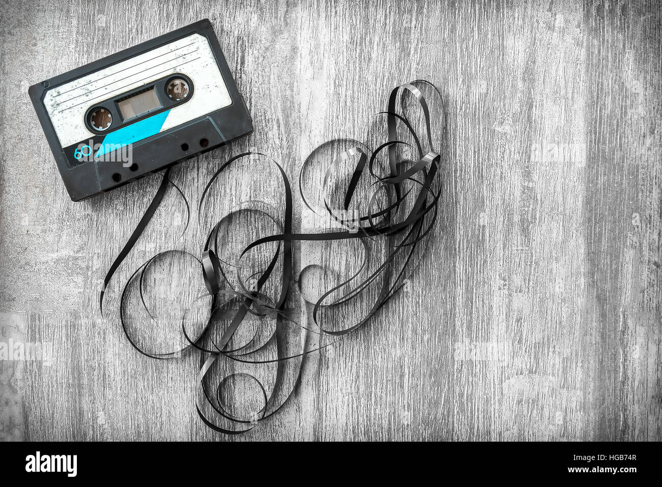audio tape rolled out background wood vintage unroll compact cassette playlist musicassette - Stock Image
