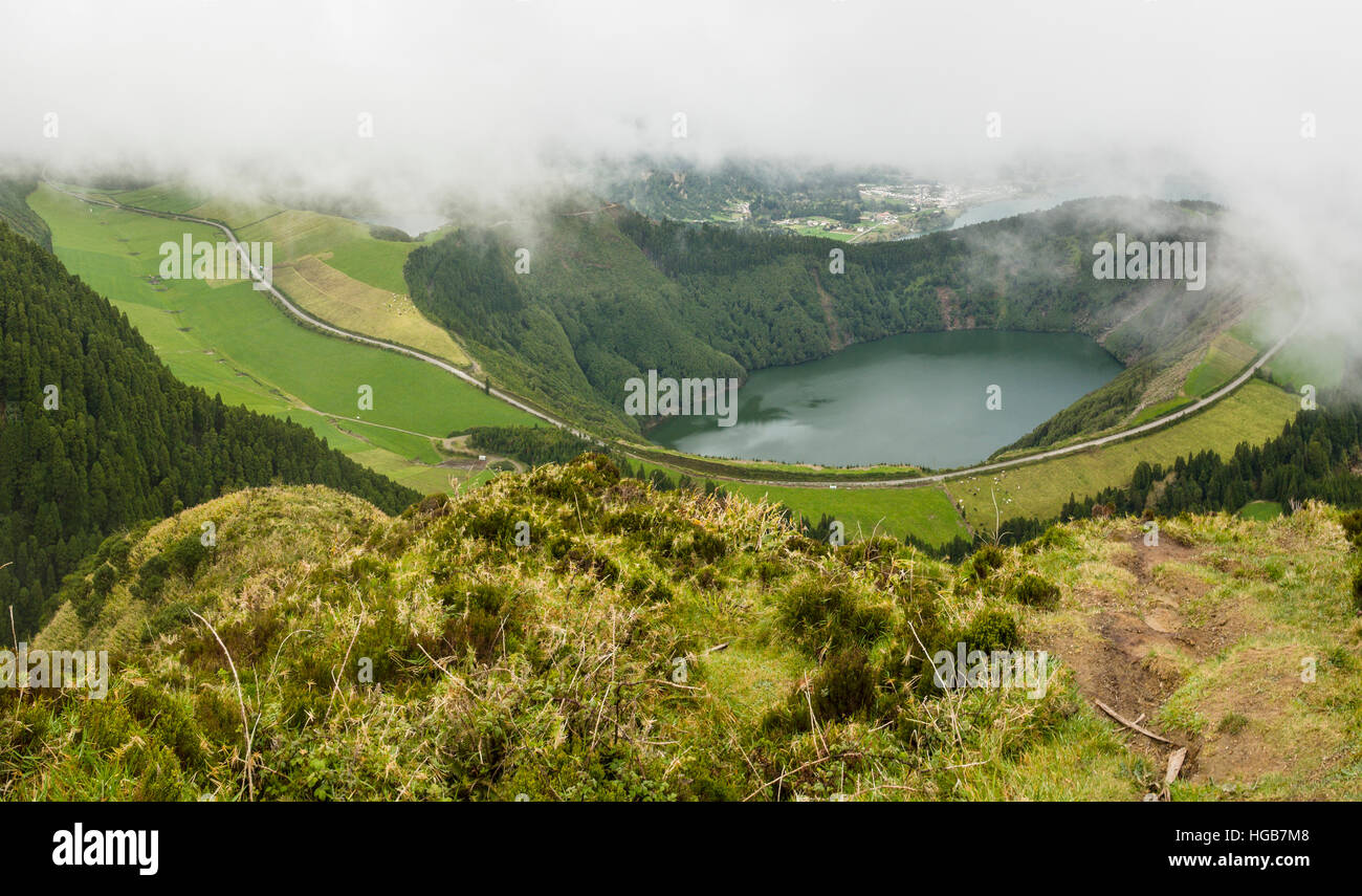 Road around Lagoa de Santiago. A curved highway loops around a lake deep in a steep old volcanic crater. Clouds - Stock Image