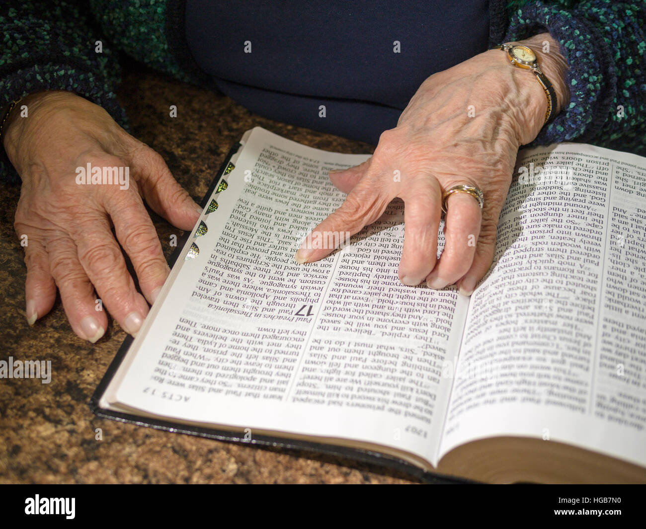 Reading a large print Bible. An old woman's arthritic and wrinkled hand and finger guiding her reading of a - Stock Image