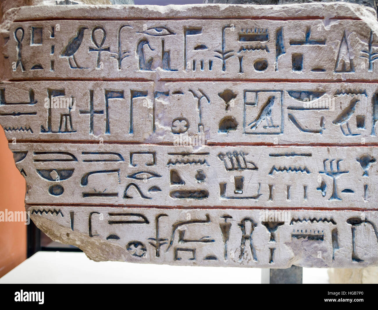 Egyptian hieroglyphs carved into stone. Four lines of hieroglyphs on a stone tablet displayed in the museum. Musee - Stock Image