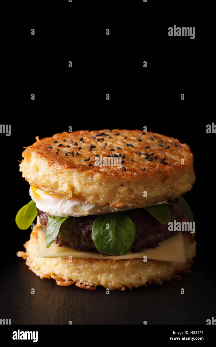 New ramen burger with beef and eggs close-up on a black background. Vertical - Stock Image