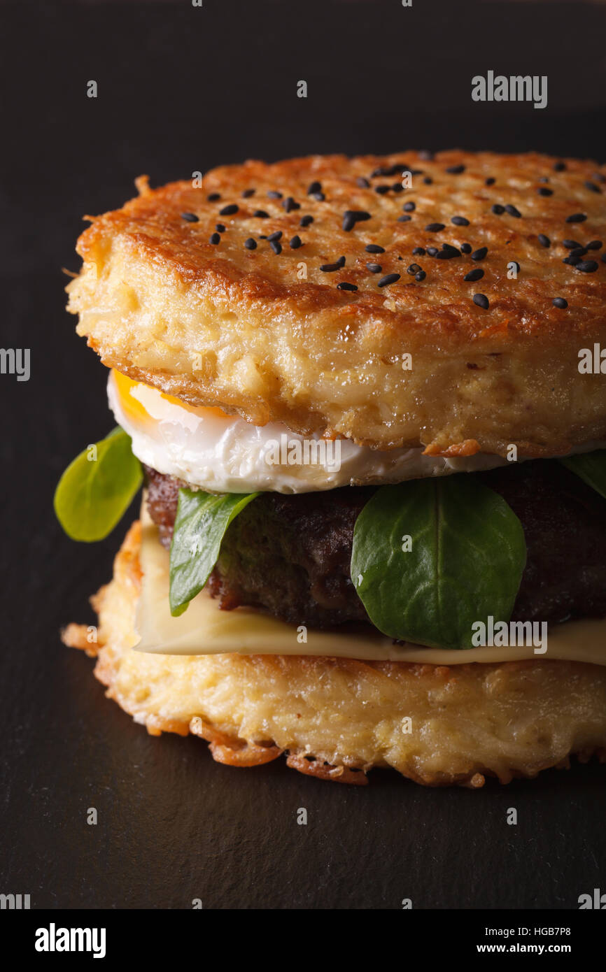 Trendy ramen burger with beef and eggs macro on a black background vertical - Stock Image