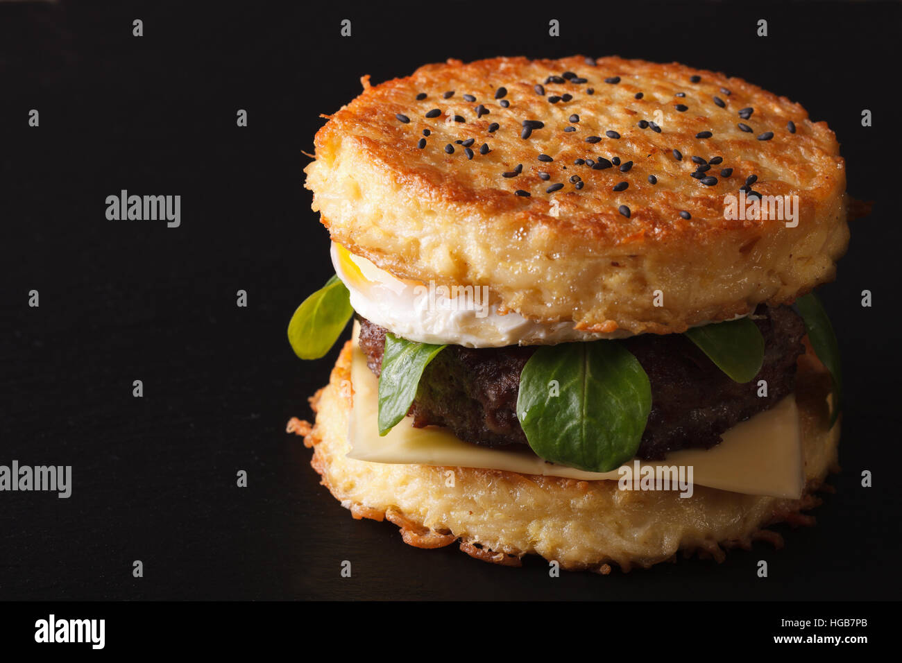 New ramen burger with beef and eggs close-up on a black background. horizontal - Stock Image