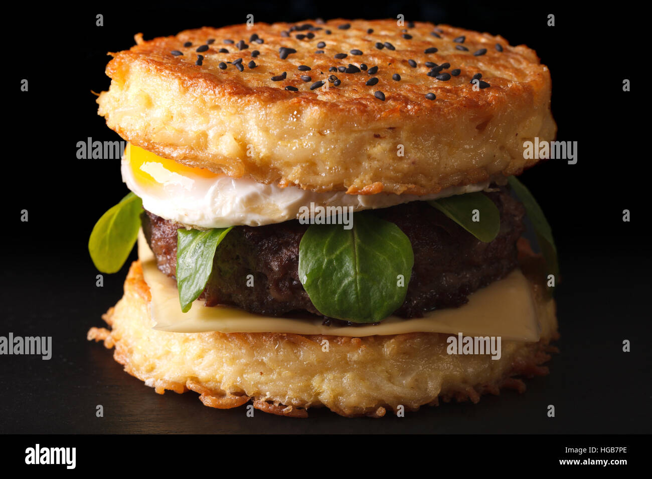 Trendy ramen burger with beef and eggs macro on a black background - Stock Image