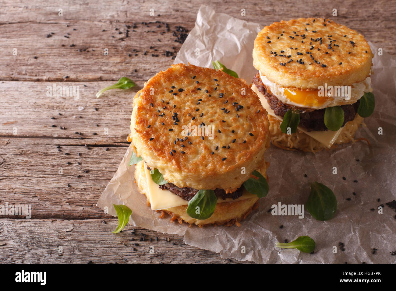 Ramen burgers with beef and egg on a paper on a wooden table closeup. Horizontal - Stock Image