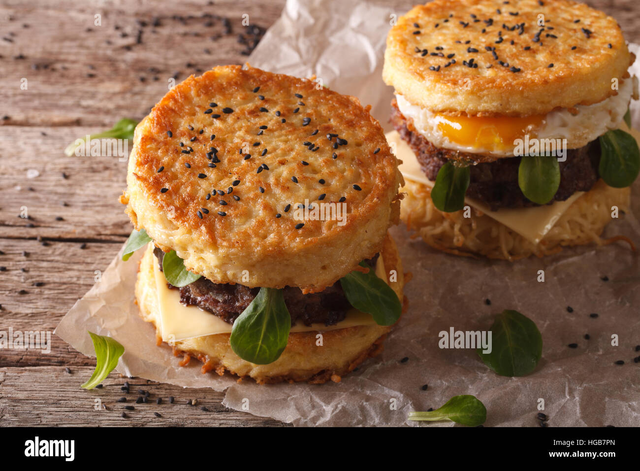 Ramen burgers with beef and egg on a paper on a wooden table. Horizontal - Stock Image