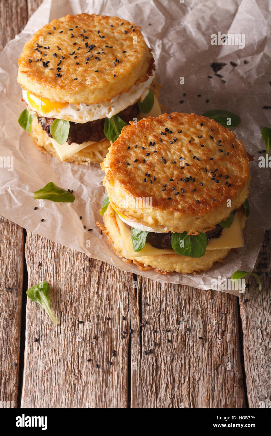 Ramen burgers with beef and egg on a paper on a wooden table. vertical - Stock Image