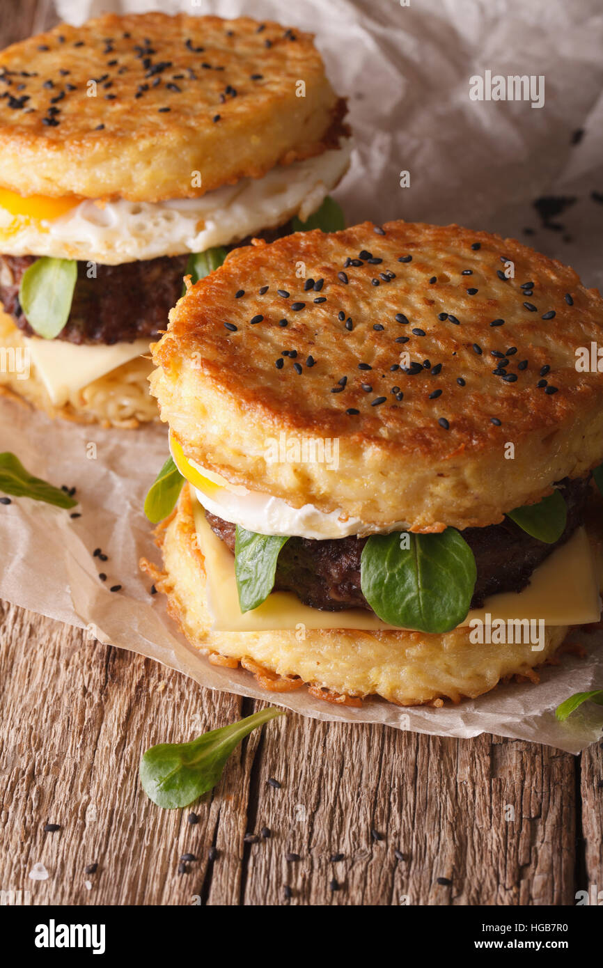 New fast food: ramen burger close-up on a paper on the wooden table. Vertical - Stock Image