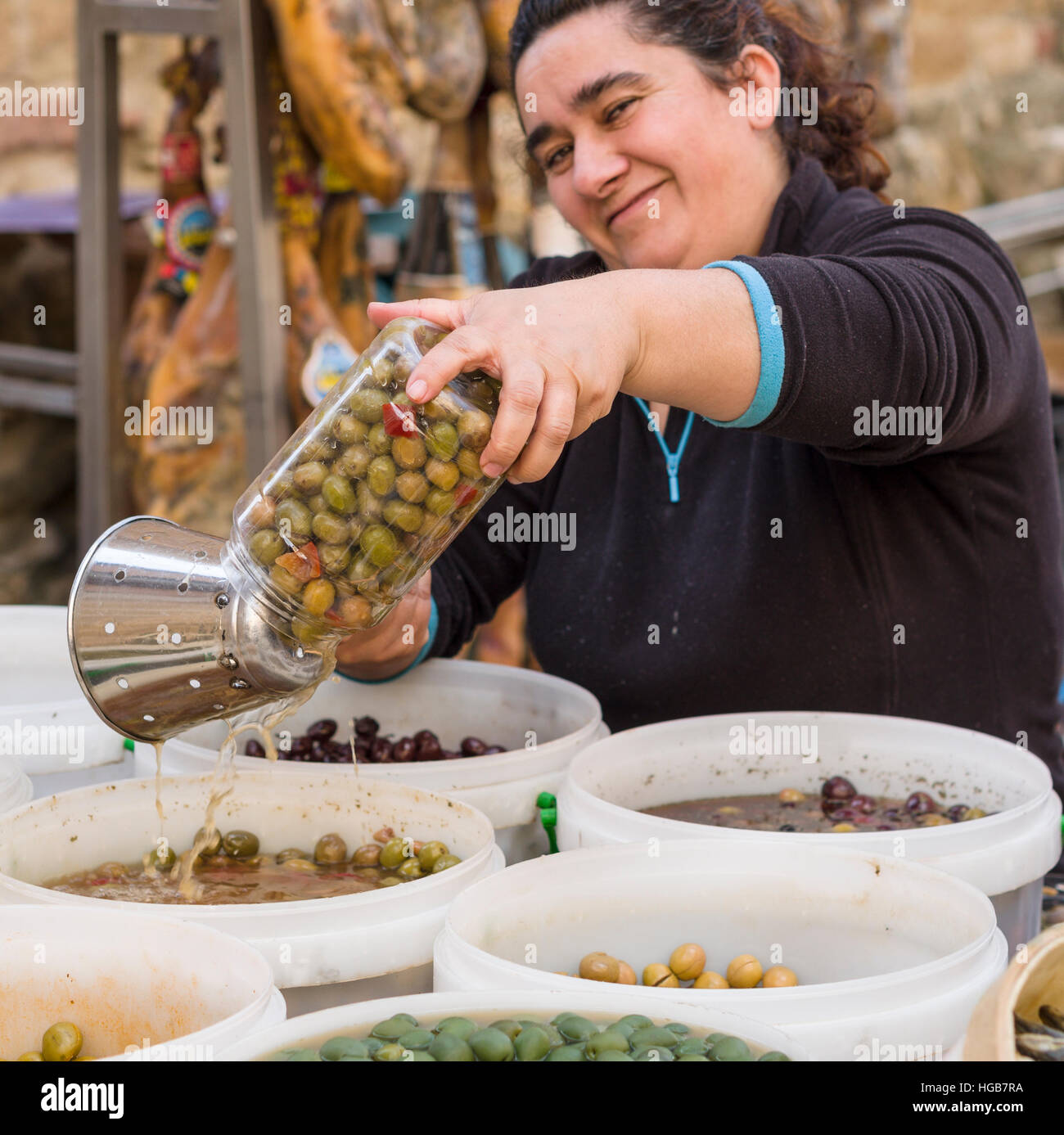 Draining Olives in the Market. A market vendor drains the vinegar from a just loaded jar of green pickled olives - Stock Image