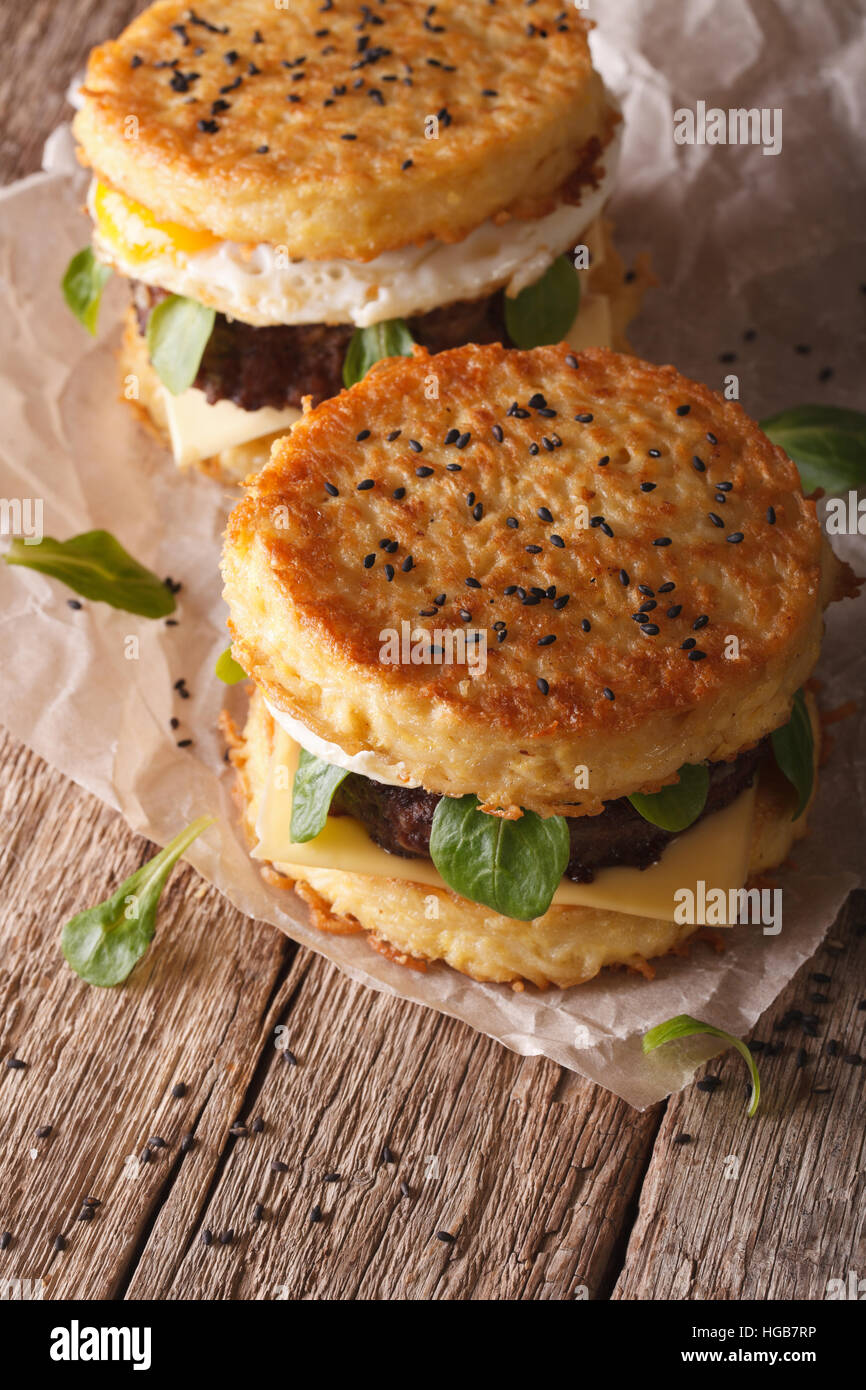 Two ramen burger close-up on a wooden table. vertical - Stock Image